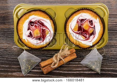 Two Cakes In Plastic Box, Tea Bags And Cinnamon Sticks