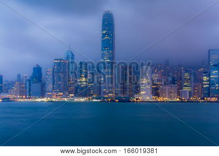 Night blurred Hong Kong business downtown with cloudy backgrounnd over Victoria Bay