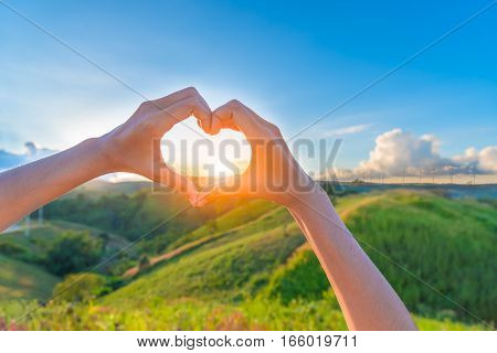 Female hands in the form of heart against sunlight behind landscape of windmills plant in blue sky Hands in shape of love heart - Love green energy.