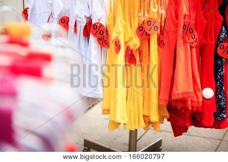 colorful clohing on a stand in front of a shop