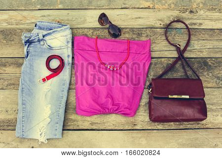 Summer women's clothing: t-shirt, beads, handbag, jeans on old wooden background. Toned image.