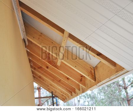 Close up on Roofing Construction. Soffit and Fascia Installation. is Usually Constructed of Vinyl Wood or Aluminum and is Installed on the Underside of Roof Overhangs and Eaves.