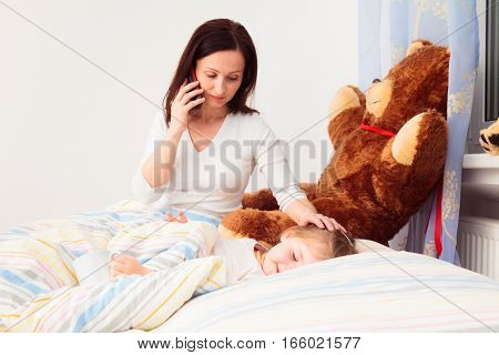 concerned mother talking on phone to a medic because of her sick daughter