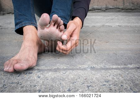 Dirty foot of a man sitting on old concrete floor. Hand of a man scratching his dirty feet.