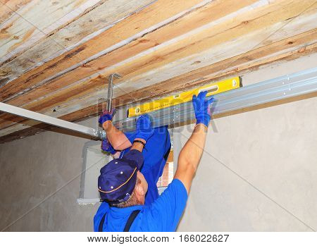 KYIV UKRAINE - February  14 2017:  Contractors Installing Garage Door Metal Profil Post Rail and Spring Installation and Garage Ceiling. Spring Tension Lifts Section Garage Door Panel that Motor does not have to Lift Entire Weight.