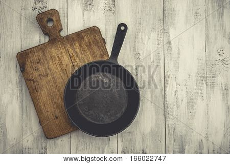 Old cast iron pan and cutting board are on the painted white table