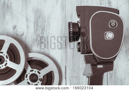 Old movie camera and film reel on the background of wooden wall