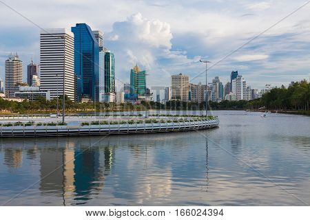 Office building with reflection over lake in public park Bangkok Thailand