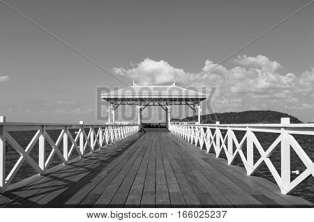Black and White Wooden walk way leading to white pavilion on the seacoast skyline Thailand