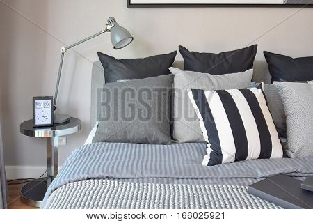 Stylish Bedroom Interior Design With Black Patterned Pillows On Bed And Decorative Table Lamp.
