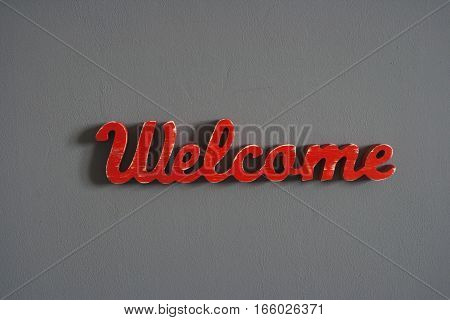 Red wooden sign on a gray wall WELCOME