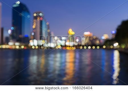 Blurred bokeh light city office building water front abstract background