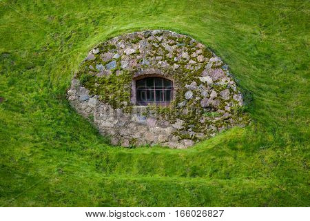 Window in a stone wall on a green hillside