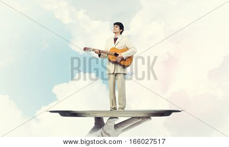 Hand of waiter presenting on tray man playing guitar