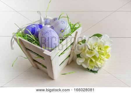 Easter small basket with colored eggs and white flower on white wooden board.