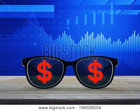 Dollar currency icon with eye glasses on wooden table over financial graph and chart Business success concept