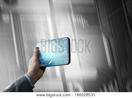 Tablet with infographs in business person hand