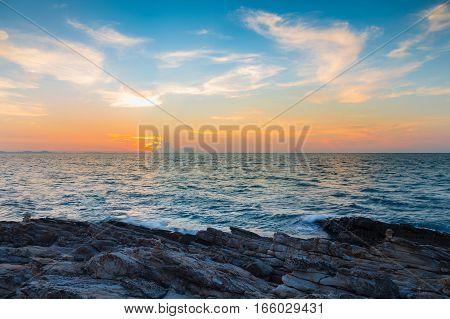 Rocky coastline with sunset skyline over the ocean natural landscape background