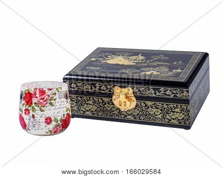 Picture of the wooden jewel-box with painting on wood and golden lock near decoupage glass isolated on white background. Painted pattern on closed box for bijouterie. Side view.
