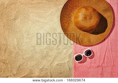 Top view of sandy beach with towel frame and summer accessories. Background with copy space and visible sand texture. Right border made of towel