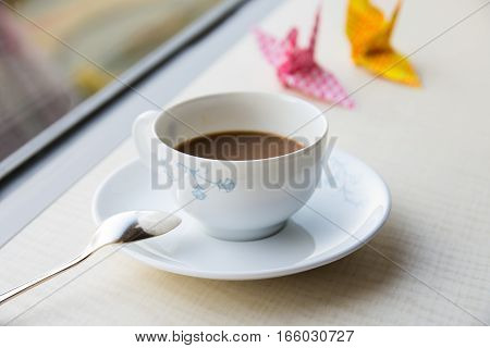 hot coffee by the window with colorful origami crane