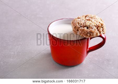 Cup of milk and wholewheat oat and coconut cookie with raisin