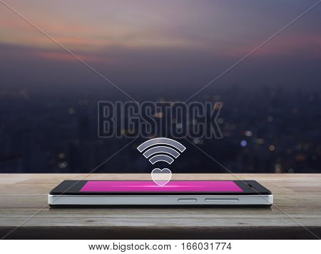 Heart wifi icon on modern smart phone screen on wooden table over blur aerial view of cityscape on warm light sundown Internet online love connection Valentines day concept