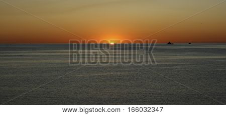 Dawn in the Mediterranean Sea in Ibiza, first ray of sunshine in a sea completely calm, artistic composition of the sun-centered image, emerging from the water, orange and yellow sky