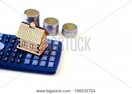 House And Calculator Againt Column Of Coin On White Background