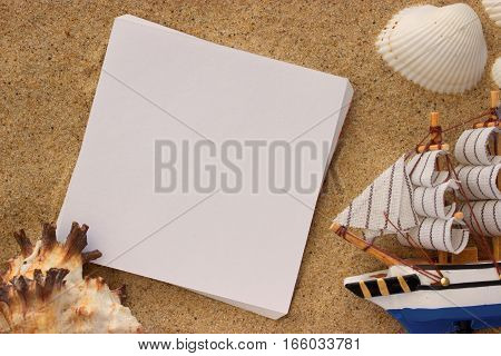 blank paper in the sand toy ship and shells