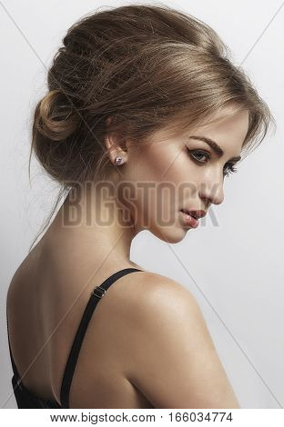 tender girl with bare shoulders. The harness at shoulder. Looking down. Profile