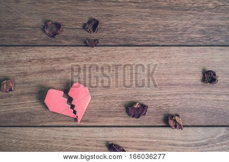 Red broken heart with dried rose petal on wooden background