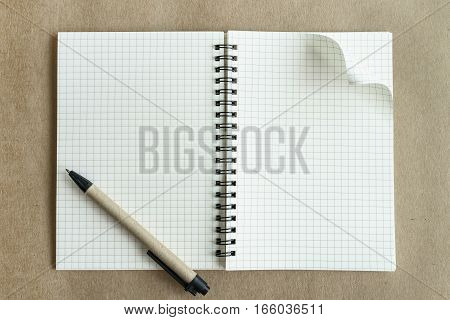 Blank notebook with pen on brown background Top view