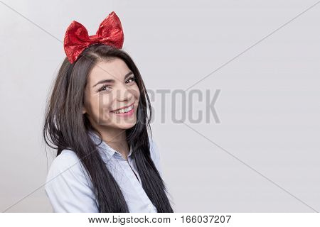 Portriat of beautiful brunette female with red ribbon