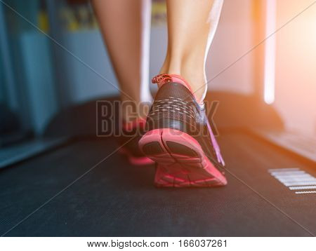 Female Muscular Feet In Sneakers Running On The Treadmill At The Gym. Concept For Fitness, Exercisin