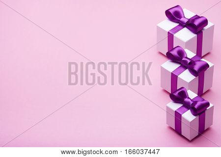 Gifts in a beautiful package, bow from satin ribbon, a few boxes with gifts, attributes festive mood, the gift set on a pink background