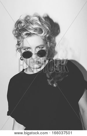 Stylish fashion sexy blonde bad girl in a black t-shirt and rock sunglasses covered with cigarette smoke. Dangerous rocky emotional woman. Black and white toned. White background, not isolated