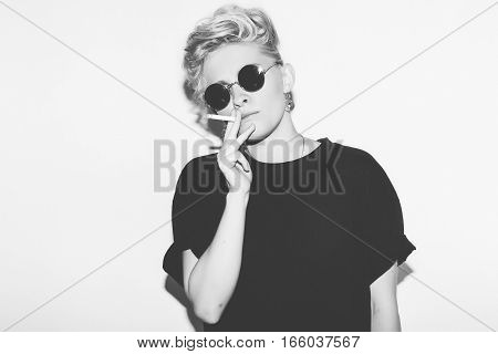Stylish fashion sexy blonde bad girl in a black t-shirt and rock sunglasses. Dangerous rocky emotional woman smokes. Black and white toned. White background, not isolated
