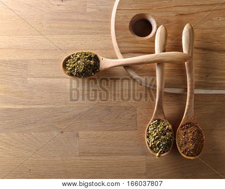 Wooden Spoons With Mixture Of Different  Spices On Kitchen Table