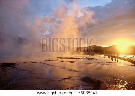 Steaming geyser at sunrise. The World Famous Grand Prismatic Spring in Yellowstone National Park. Jackson Hole. Wyoming. United States.