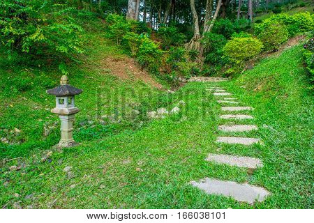 Asian traditional lamp in a garden with lush lawn and stone pathway