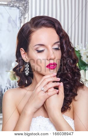 Beautiful bride with fashion wedding hairstyle and red lips .Closeup portrait of young gorgeous bride. Wedding. Studio shot .Happy Bride waiting groom. Marriage Wedding day moment
