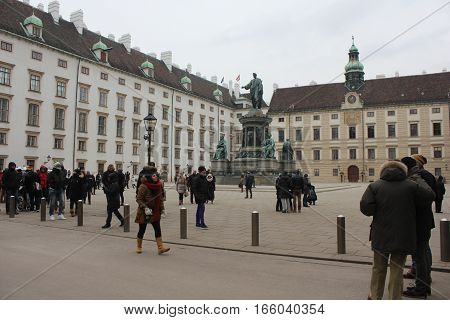 VIENNA, AUSTRIA - JANUARY 3 2016: People in Hofburg Palace in Vienna in a cloudy day with emperor Franz statue