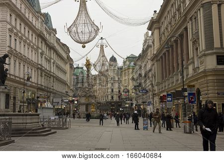 VIENNA, AUSTRIA - JANUARY 3 2016: Vienna city centre at day time in winter season: Graben street full of people with Pestsaule monument in the foreground