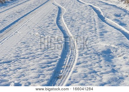Car tyre trails in the snow, winter background