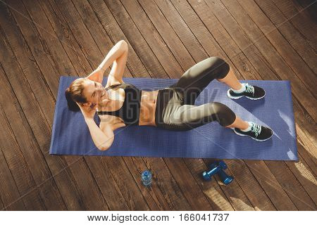 Young athletic woman training hard with gym exercise at home, lying at mat. upper view