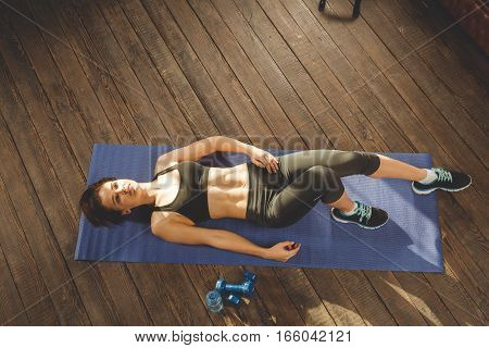 Young athletic woman resting between workouts at home, lying at mat. upper view