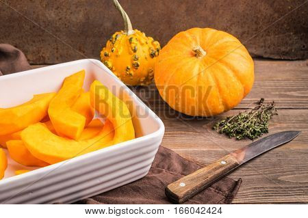 Ripe peeled pumpkin cut into slices in a white bowl for baking on the kitchen table . Dark wooden background.