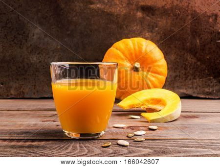 Fresh pressed juice from ripe pumpkin in a transparent glass goblet. Dark wooden background.