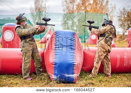 Paintball sport player girls in protective camouflage uniform and mask with marker gun outdoors